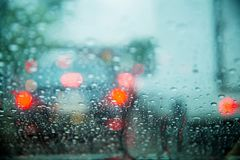 Drop on glass at twilight time while raining.View side out the car.Rain drops on window with road light bokeh,. City life in rainy season abstract background stock images