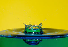 Drop movement. Macro of drop movement - Yellow background Royalty Free Stock Photography