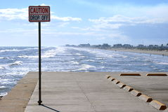 Drop off board walk end. The end of the board walk in Galveston, Texas showing a rather obvious drop off sign before the ocean starts. Waves roll in from the Royalty Free Stock Photo