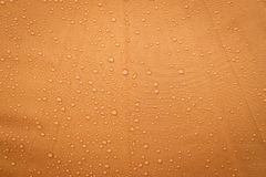 Drop on orange background. Abstract background of rain water drop on orange umbrella background Stock Photo