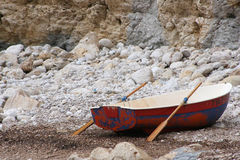 Drop out. Rowing boat on a desolate beach Royalty Free Stock Photos