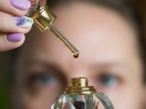 A drop of perfume on a glass stick. Arabian oud attar perfume or agarwood oil fragrances in glass bottles royalty free stock image