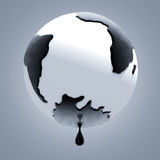 Drop of petroleum falling from planet earth Royalty Free Stock Photography
