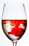 Drop of red color spreading in wine glass Royalty Free Stock Photography