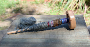 Drop spindle for spinning sheep wool into yarn. Wood drop spindle with natural sheep wool fiber twisted yarn wrapped around the dowel. The yarn is gray, blue stock photos