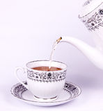 Drop tea from teapot to teacup Stock Images