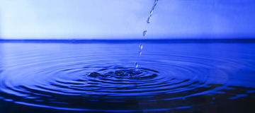 Drop water in deep blue background Stock Photography