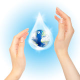 Drop of water with Earth. Drop of water with Earth inside and hands on white. The symbol of Save Planet stock image