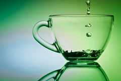 Drop of water falling down to cup of tea Royalty Free Stock Photo