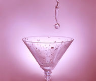 Drop of water falling in martini glass Royalty Free Stock Photo