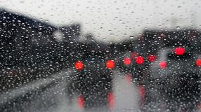 Drop water raining and red bokeh traffic jam on rode way, background concept. stock photos