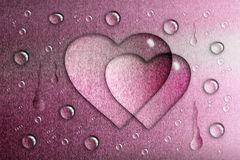 A drop of water in the shape of a heart, a pink metallic backgro. Und, a matte texture Royalty Free Stock Photo