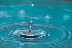 Drop of water splash in turquoise background Royalty Free Stock Photography
