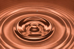 Drop of water, water splash in Brown color. Royalty Free Stock Images