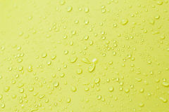 Drop of water on yellow background. Royalty Free Stock Photography