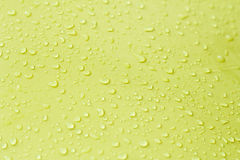 Drop of water on yellow background. Stock Image