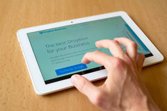 DropBox. Man's hand use with his fingers tablet. Dopbox homepage is on the screen. Dropbox is popular file sharing system, cloud royalty free stock image