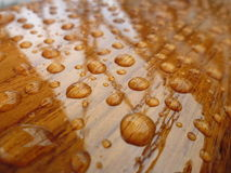 Droped water on varnished wood Royalty Free Stock Photos