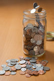 Droping coins into a jar Royalty Free Stock Images