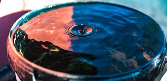 Droplet blue red water bucket Stock Photography