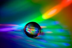 Droplet on CD. A water droplet on a compact disk Stock Photo