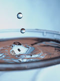 Droplet falling in the blue water Stock Photo