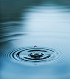 Droplet falling in blue water Stock Photos