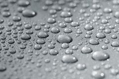 Droplets on car. Droplets on a car. Short depth of field. The image may appear grainy, but it's caused by the metallic paint Stock Images