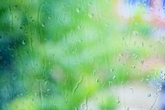 Droplets of rain on a window. Droplets of rain water on a window glass on a blurred background and trees with green foliage Royalty Free Stock Photos