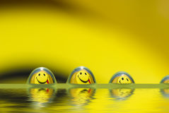 Droplets team. Funny water droplets with smiley reflection royalty free stock photography