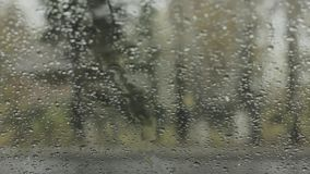 Droplets on a windshield on the day snow with rain. Blurred background.  stock footage