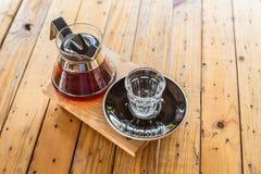 Droppandekaffekopp och kaffekruka på den wood tabellen arkivbild