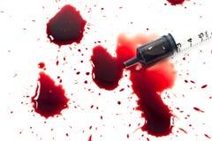 Droppar av blod och en injektionsspruta Arkivbilder