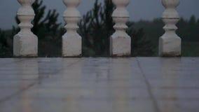 Droppar av den Heavy Rain nedgången på de vita tegelplattorna av balkongen arkivfilmer
