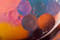 Droppar av olja på vatten Arkivfoto