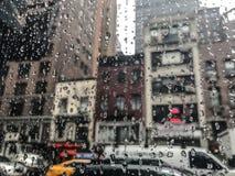 Droppar av regn på ett fönster med en stadssikt Arkivfoton