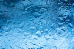 Droppar av regn på ett fönsterexponeringsglas färg arkivfoton