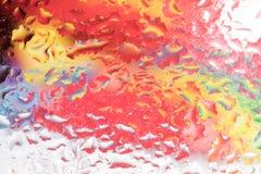 Droppar av regn på ett fönsterexponeringsglas färg Fotografering för Bildbyråer