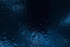 Droppar av regn på ett fönsterexponeringsglas färg Arkivbild