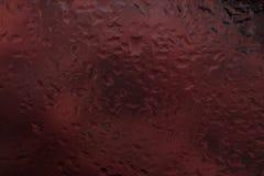 Droppar av regn på ett fönsterexponeringsglas färg arkivfoto