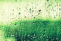 Droppar av regn på exponeringsglas på grön bakgrund Grönska gräsplan: Pantone färg - trend 2017 Royaltyfria Bilder
