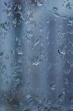 Droppar av regn på fönstret, regnig dag, oskarpt staket i baksidan Arkivbild