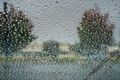 Droppar av regn på vindrutan; molnig himmel och hösten färgade träd i bakgrunden Royaltyfri Fotografi