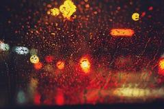 Droppar av regnduggregn p? exponeringsglasvindrutan i natten Gata i h?llregnet arkivbilder
