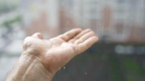 Droppar av regnnedgången in i händerna av en ung man lager videofilmer