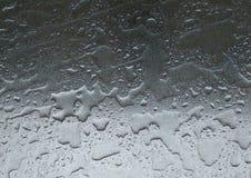 Droppar av regnvatten på bakgrund för metallyttersida - nära övre skinande metallyttersida som täckas i vattensmå droppar efter r Royaltyfri Fotografi