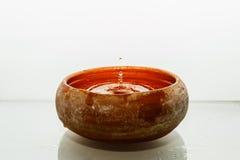 Droppar av vatten i en lerakruka Arkivbild