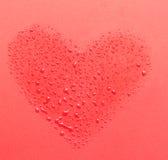 Droppar av vatten i form av hjärta på en röd bakgrund Arkivbilder