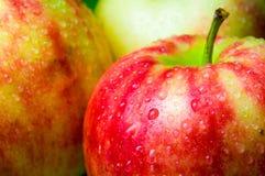 Droppar av vatten på en äpplecloseup på en bakgrund av äpplen Fotografering för Bildbyråer