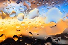 Droppar av vatten på en färgbakgrund grunt djupfält Se Royaltyfri Bild